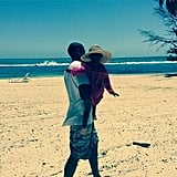 And her dad carried her across the beach as she stayed shaded in a straw hat.