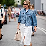 Styling a white dress and denim jacket with a beige pair of Havaianas.