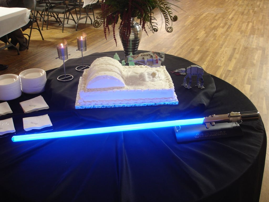 A lightsaber leads the way to a lovely white Star Wars cake.  Source: Flickr User Klobetime