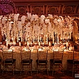 Orchids cascading from a centerpiece raised above the table creates such a romantic vibe.