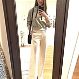"""Dana styled her gray hoodie with white trousers, pointed-toe boots, and a crossbody bag. """"I love mixing sporty pieces into my wardrobe in unexpected ways, such as dresses with sneakers, a varsity jacket over a dress, or a cozy hoodie with a blazer. I always try and create a balance with accessories that are elevated and tailored,"""" she says."""