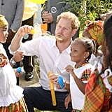 Harry blew bubbles with a group of kids during his visit to Antigua in November 2016.
