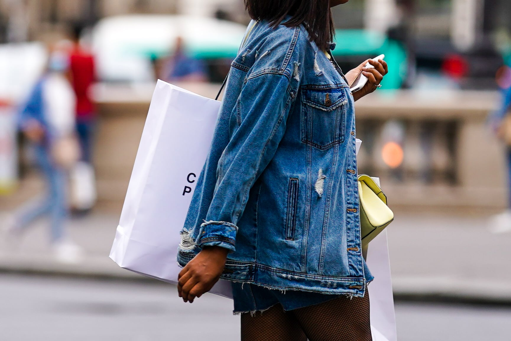 PARIS, FRANCE - JULY 04: A passerby wears a blue ripped denim jacket, a yellow bag, a large white paper shopping bag, on July 04, 2020 in Paris, France. (Photo by Edward Berthelot/Getty Images)