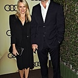 Naomi Watts stuck to a chic black minimalist styling M.O., donning a black cocktail dress with a structured black blazer, a quilted clutch, and cutout heels.