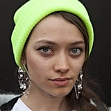 A casual neon green beanie and stunning earrings gave this off-duty look instant interest.