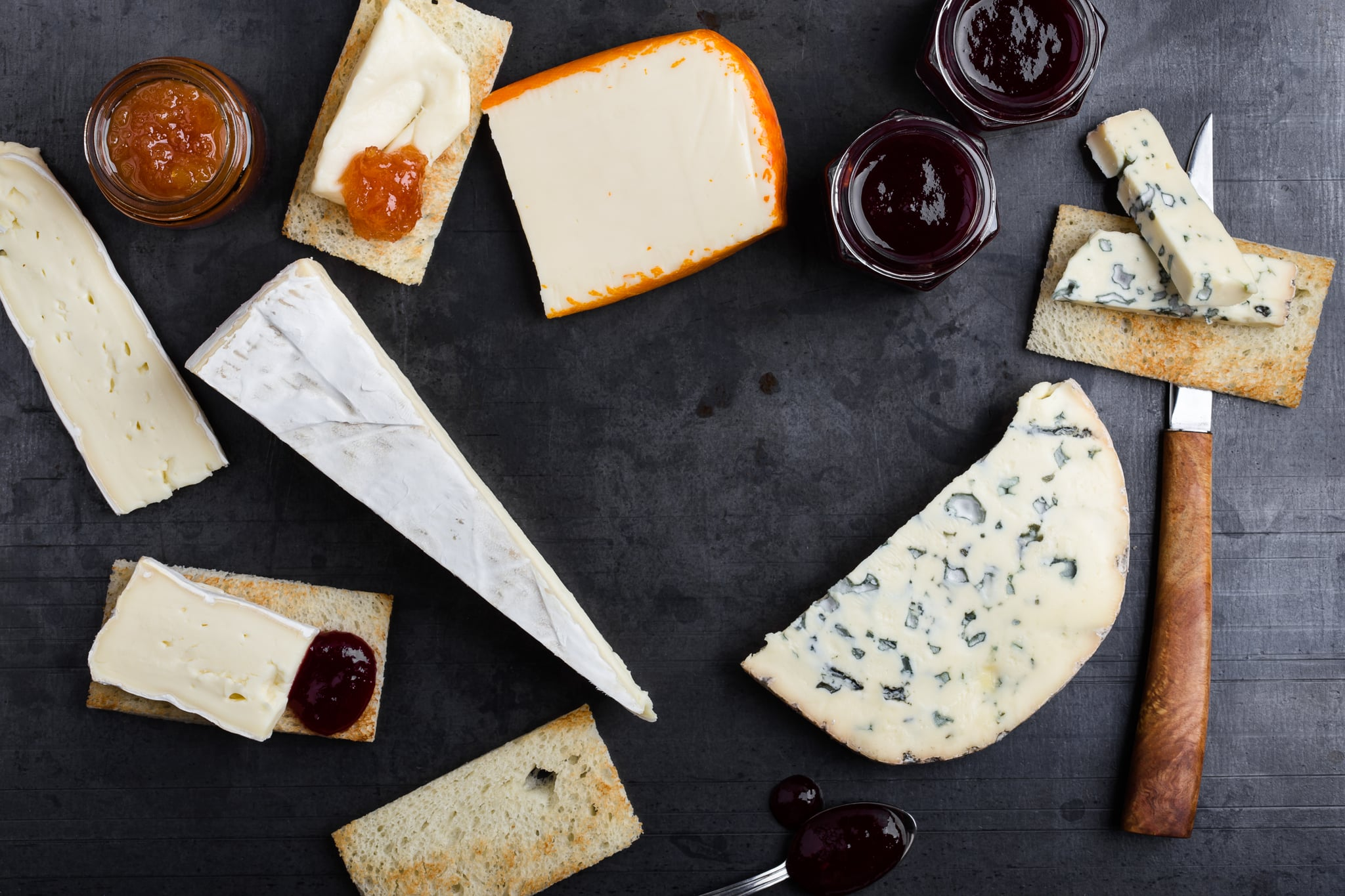 Various types of French cheese with jam over gray background viewed from above. Creamy Saint Paulin cheese, brie, Fourme d'Ambert blue cheese