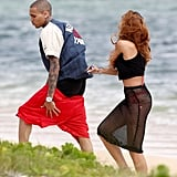 Rihanna covered up her pink bikini with a black cover-up to hit the beach with Chris Brown in Hawaii.
