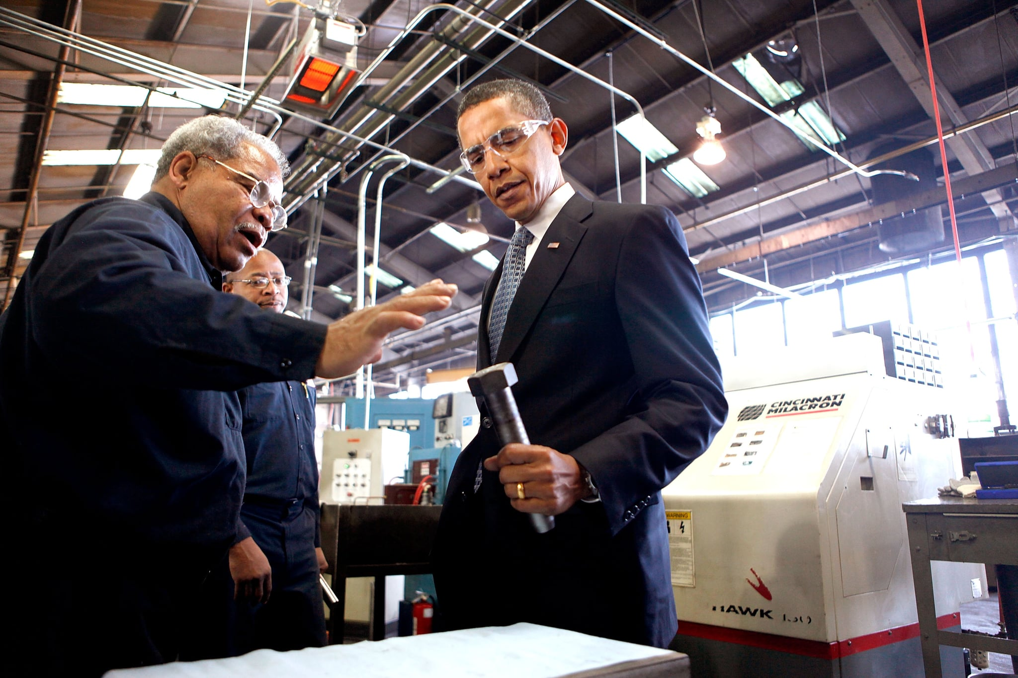 A worker shows Obama how he makes large bolts used for bridge construction.