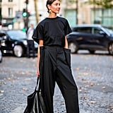 Give your black tee a fresh feel by pairing with structured pants and sleek slides.