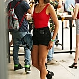 Nina Dobrev wearing an Aritzia bodysuit, denim shorts, Lili Claspe choker, and boots at the festival.