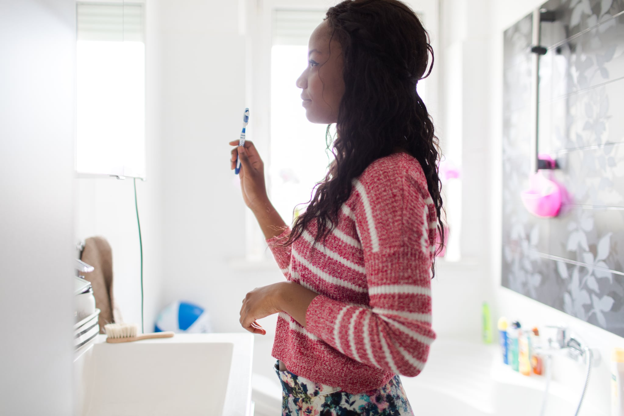 Young woman in bathroom, brushing her teeth and doing her morning hygiene as a part of getting ready for a new day to start!