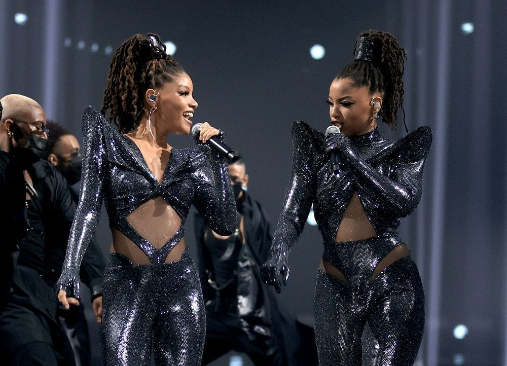 "If you told me Chloe x Halle descended upon the 2020 People's Choice Awards in a flying saucer, I would believe you. The singing duo looked like the otherworldly, intergalactic goddesses they are while performing ""Ungodly Hour"" at the award show on Sunday. Styled by Zerina Akers, Chloe and Halle wore shimmering, custom-made jumpsuits by Rey Ortiz. Though each outfit was distinct, they both featured accentuated shoulders, various cutouts, and thick ponytail holders in the same material.  This stylist showing is of course only the latest in a series of from the sisters, who have perfected the virtual performance space since the release of their sophomore album this summer. Chloe and Halle's performance outfits have included metallic bodysuits resembling armor, strappy separates in a reflective fabric, and latex — lots of latex. They also paid tribute to the Spice Girls with their fun looks for the GLAAD Media Awards. See photos from this new fashionable appearance ahead.      Related:                                                                                                           Fashion Icon Tracee Ellis Ross Talks the Power of Style: ""I Wear My Insides on the Outside"""