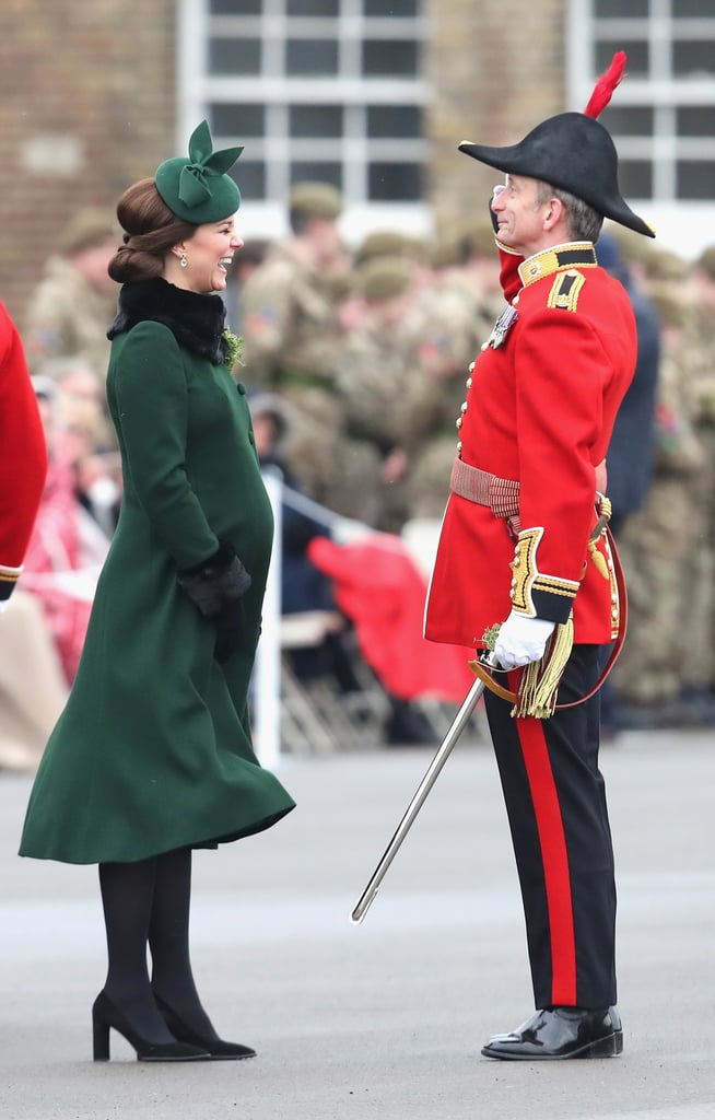 Kate Middleton and Prince William made their annual appearance at the 2018 St. Patrick's Day Parade in the UK on Saturday to honor the Irish Guards. Kate, who is expected to give birth to their third child next month, looked regal in a festive green coat trimmed with black fur cuffs and a black fur collar. Prince William looked equally dapper in his traditional ensemble as well. During their visit, Kate and William got in on the celebrations with a pint of Guinness for William and a glass of water for Kate, of course. Kate also petted the regimental wolfhound mascot outside while flaunting her growing baby bump. Keep reading to see more photos from their fun outing, then see all of their cutest family moments over the years.