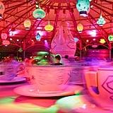 Teacups spin under colored lights.
