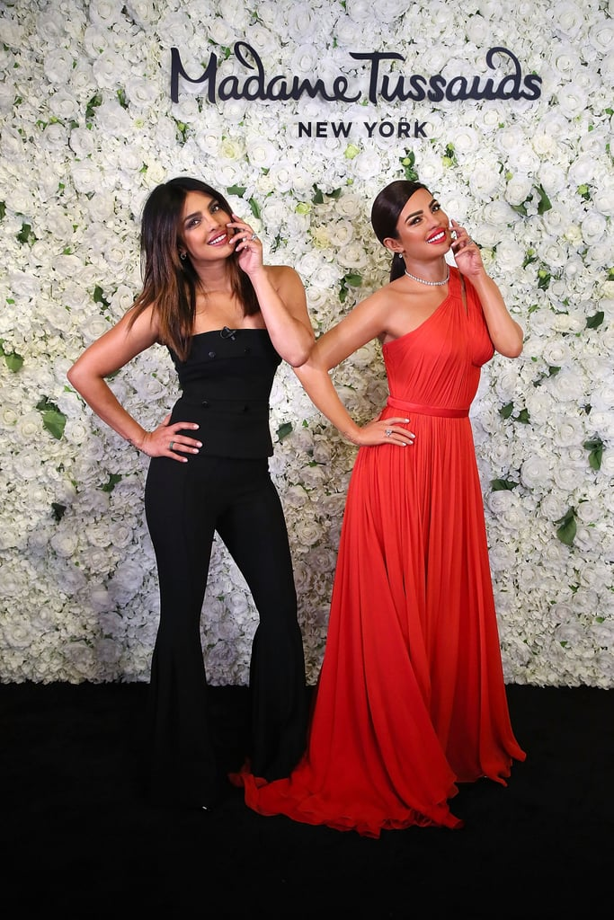 """If Priyanka Chopra ever needs a stand-in on the set, or maybe a decoy to take her place during dinner with Nick Jonas, she should definitely employ this eerily spot-on wax figure. On Wednesday, the newly-married Isn't It Romantic actress helped unveil her official wax figure at Madame Tussauds in NYC. Clad in a glamorous red gown and diamond jewellery, the statue is also striking a sultry pose, which Priyanka copied while posing for photographers. Priyanka should consider herself pretty lucky, as not all celebrities have such stunningly similar wax figures to show off. Before meeting her mirror image this week, Priyanka stopped by The Tonight Show Starring Jimmy Fallon and revealed the couple nickname she wants to go with: """"Prick."""" OK sure, let's do it! Keep reading to see photos of Priyanka and her evil doppelganger wax figure."""