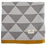 The contrast of gray and cream triangles with mustard yellow trim makes Ferm Living's Little Remix Blanket ($79, originally $93) a chic choice for modern moms and babies.