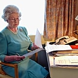 Queen Elizabeth II reviews papers on her train in 2002.