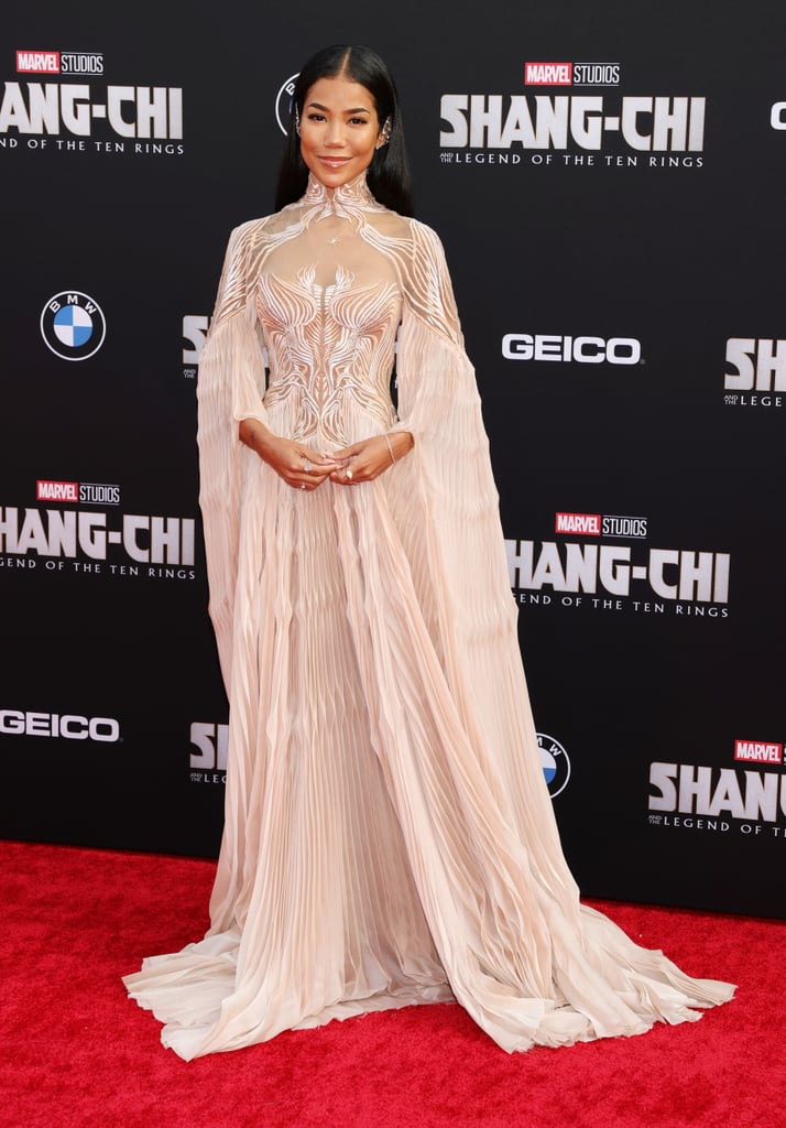 """Nothing announces your arrival on a red carpet like a stunning head-turning outfit, and Jhené Aiko certainly understood the assignment. On Aug. 16, the singer attended the premiere of Shang-Chi and the Legend of the Ten Rings, Marvel's first-ever Asian superhero movie, wearing an intricate gown fit for an ethereal goddess. Between the impeccable trippy embroidery, dramatic sleeves, and mismatched pleats made from upcycled marine debris, it's hard not to be mesmerized by Jhené's Iris van Herpen dress, straight from the designer's spring 2021 couture collection.  We imagine all eyes were on that futuristic design practically drawn onto her body, so it only makes sense that Jhené kept the rest of her look simple, opting for delicate rings and bracelets, as well as sparkly ear cuffs. The singer, who features on the film's soundtrack with Swae Lee, also shared photos from the occasion on her Instagram afterwards, writing, """"woah! @shangchi was so good!"""" Ahead, see the star's enthralling gown from all angles.      Related:                                                                                                           Oh, the Many Stars Who've Fallen Under the Hypnotizing Spell of the Sexy """"Wet Look"""" Dress"""