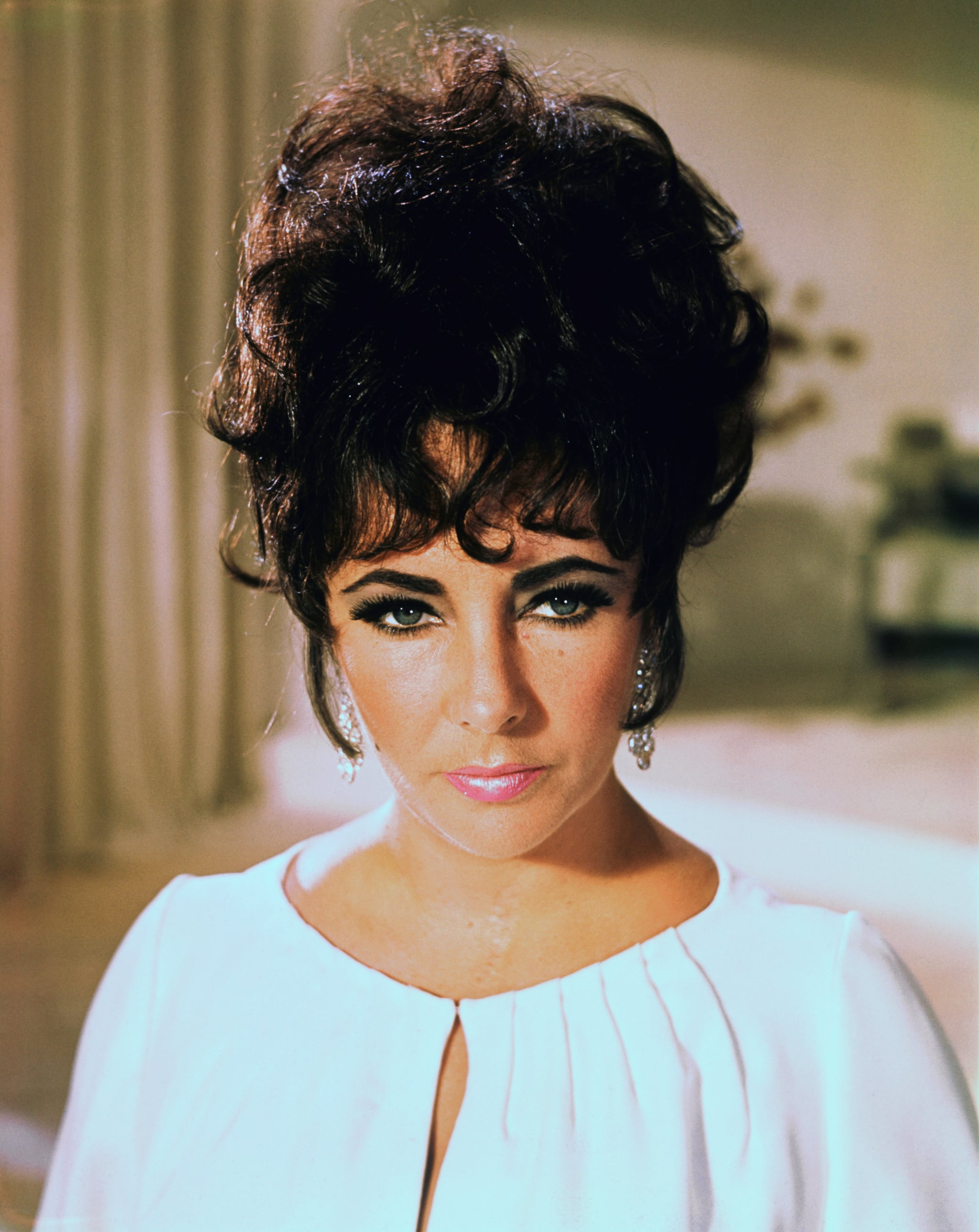 Publicity handout of actress Elizabeth Taylor, shown from the shoulders up, wearing a white dress, with her hair pinned up loosely to form a bouffant. Undated photograph.