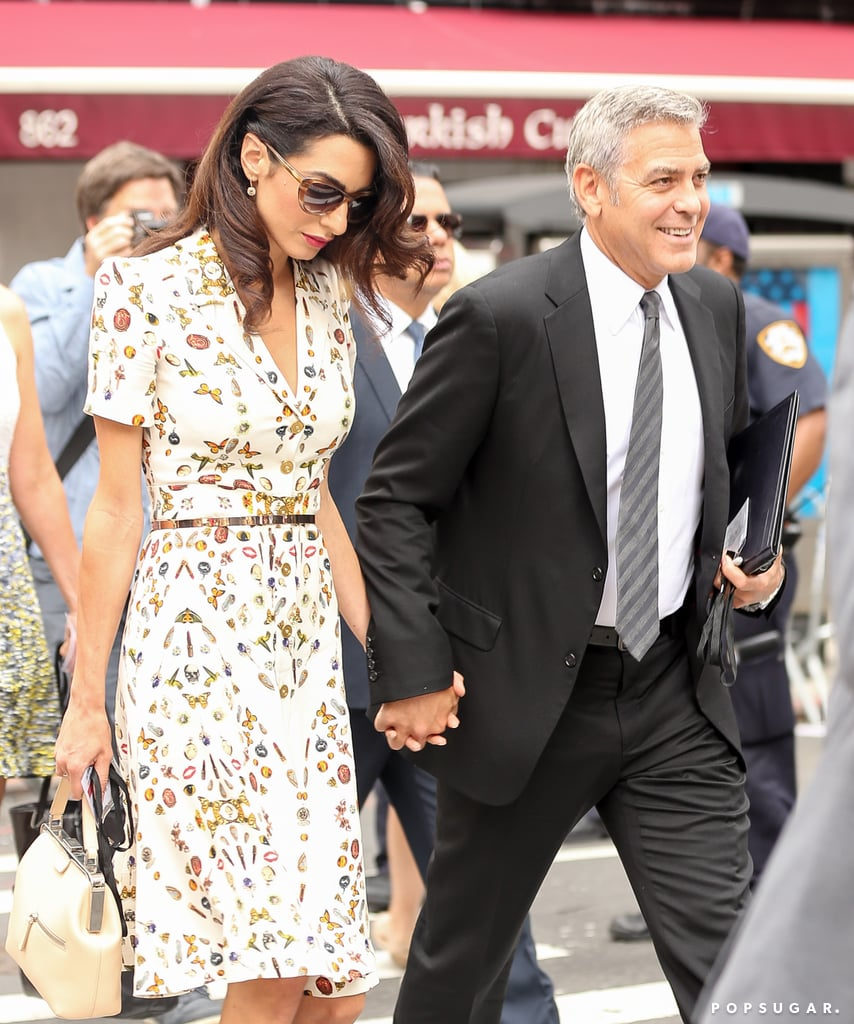 """George Clooney was all smiles while out and about with his wife, Amal, in NYC on Tuesday. George held on tightly to Amal's hand as they crossed the street and chatted among themselves. Later in the day, George attended the Leaders Summit For Refugees at the United Nations, where he was surprised with the news about Brad Pitt's divorce by a reporter while doing press for the event. In addition to their cute PDA, the couple looked like they meant business; George donned a black suit complete with a gray tie and clutched a folder, while Amal kept things classy in a short-sleeved dress and heels. Earlier this week, Amal, a human rights attorney, appeared on the Today show, and revealed that George was worried about her safety when she took ISIS leaders to trial. """"You know, this is something I discussed with my husband before I took on something like this . . . We did discuss it, and we are aware of some of the risks involved, of course,"""" she said. Just another one of their many cute moments together."""