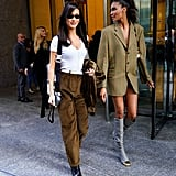 Bella Hadid wearing a white top with brown suede pants and tiny sunglasses. Cindy Bruna opted for a blazer dress with thigh-high boots.