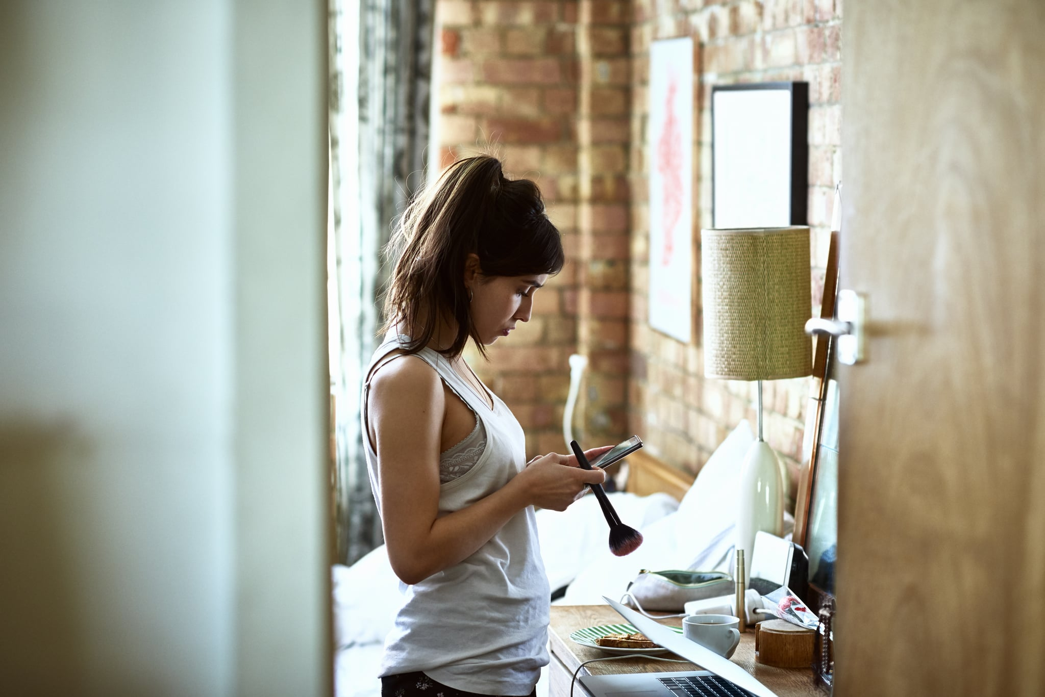 Woman in her 20s getting ready in the morning, laptop half open, reading text message