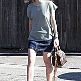 Elle went for a high-low look by covering the top of her skirt with a loose gray tee and completing her outfit with her Louis Vuitton bag.