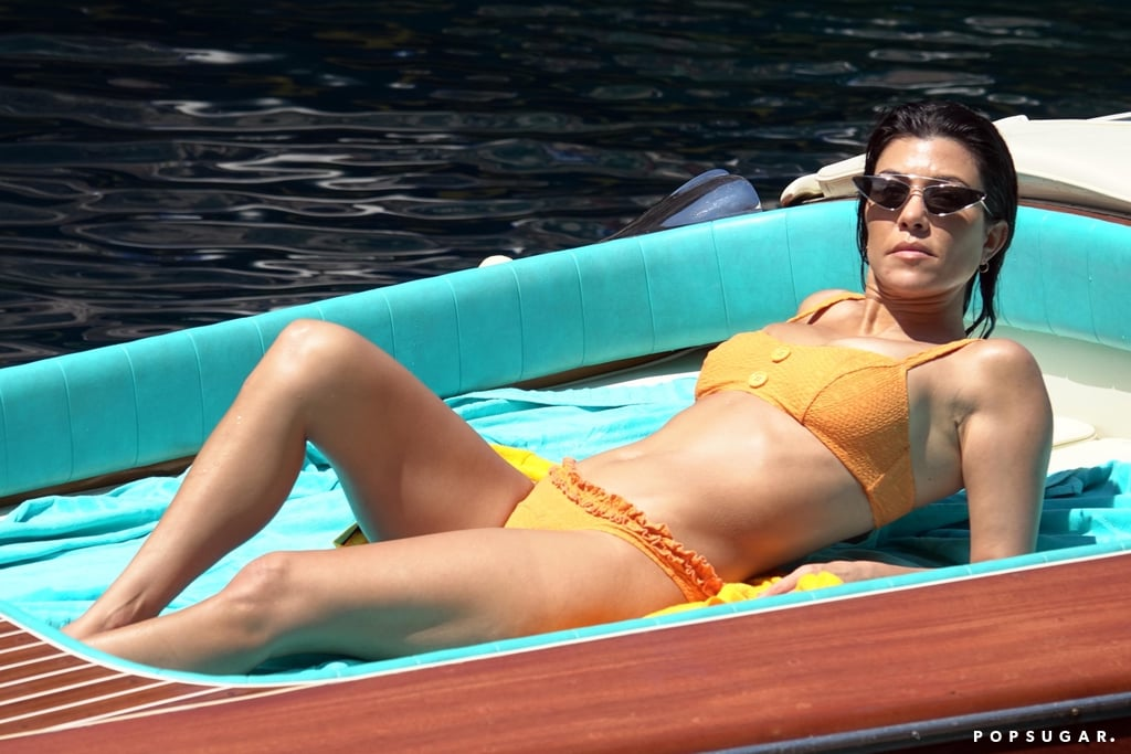 Kourtney Kardashian continues her enviable vacation streak. After her recent serene trip to Utah, the 39-year-old star traveled to Italy with her boyfriend, Younes Bendjima. The couple soaked up some sun while touring Capri by boat, and Kourtney was spotted wearing a retro orange bikini by Lisa Marie Fernandez.  Kourtney is one of the many celebrities to wear a bikini by the designer. Just last Summer, Kourtney's sister Kendall Jenner wore a similar Lisa Marie Fernandez bikini in pink. Kourtney styled hers with futuristic Prada Ultravox Eyewear ($440) sunglasses and a classic straw hat. Interested in getting an energizing tangerine bikini for yourself? Shop our favorite selections ahead and then get even more swim-spiration by browsing Kourtney's other bikini looks.       Related:                                                                                                           We Don't Need to Keep Up With Kourtney Kardashian to Know She Owns the Best Swimsuits