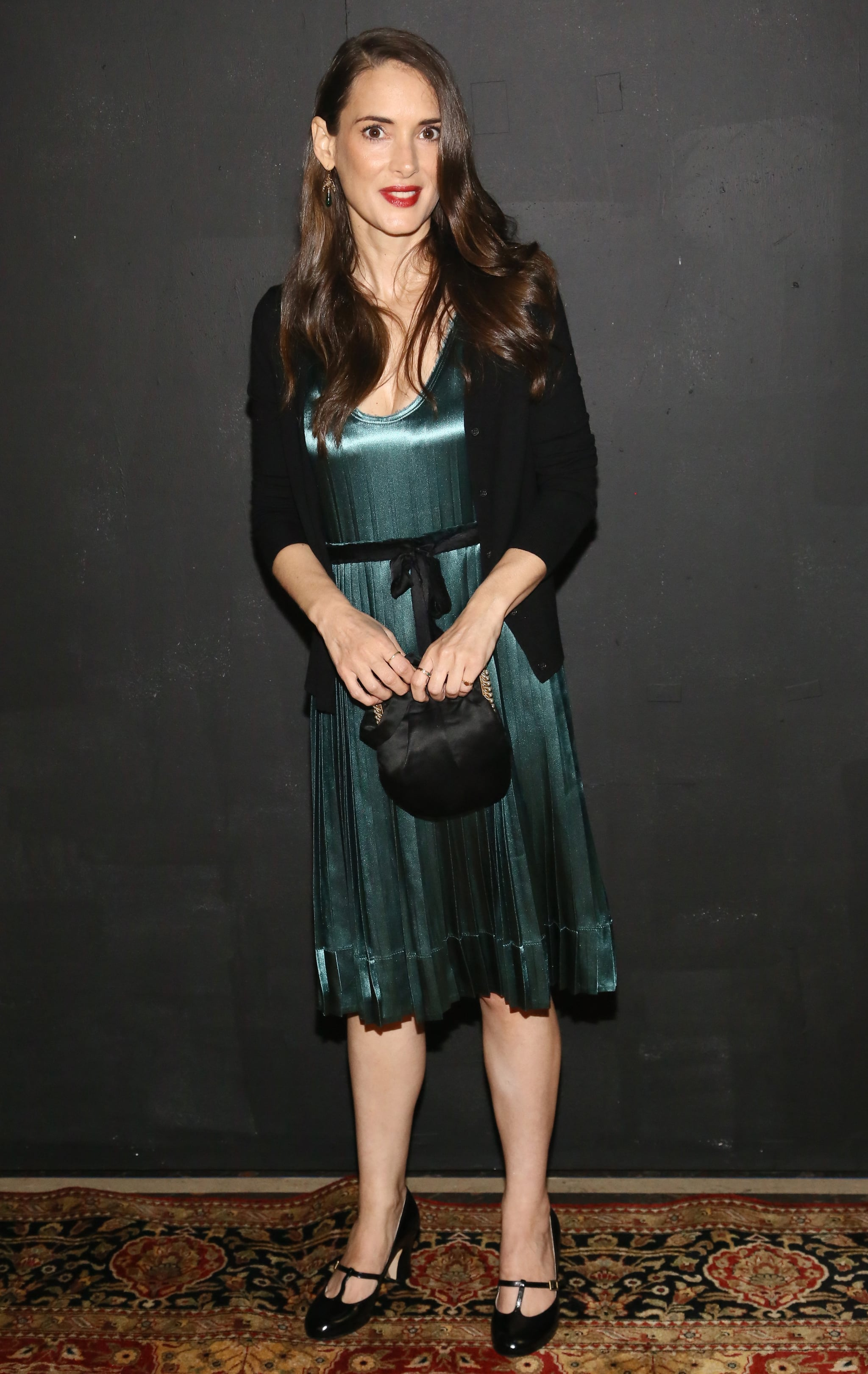 Winona Ryder showed her support for Marc Jacobs in a silky pleated green dress and a black cardigan.