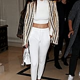 Gigi showed up to the Balmain show in a cozy white Jonathan Simkhai turtleneck, track pants, her go-to low-top sneakers, and a shimmering blazer balanced on her shoulders.