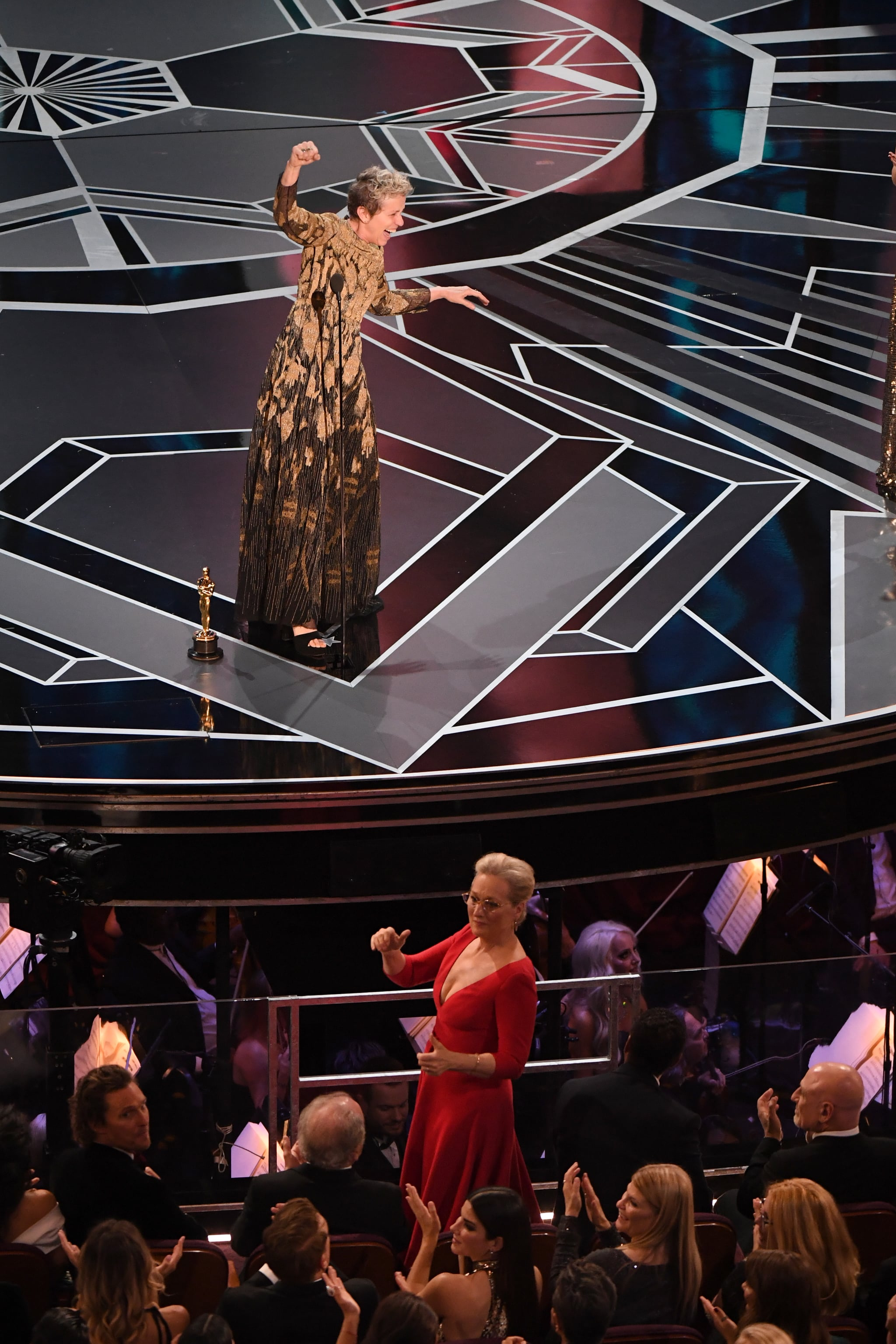 US actress Frances McDormand (back) calls for women nominees to stand up as she delivers a speech after she won the Oscar for Best Actress in