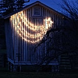 I love the contrast of this simple barn facade decorated with such stylish lights.  Source