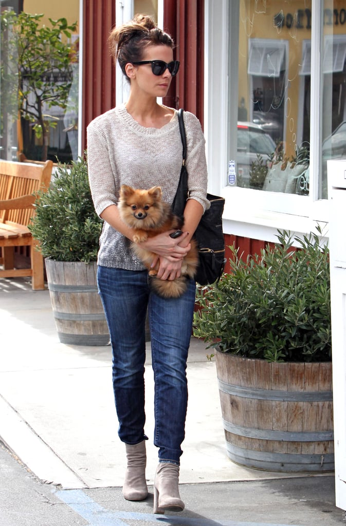 Jeans and ankle boots are staples of her weekend style. A thin sweater up top avoided extra bulk, and the pup was just plain cute.