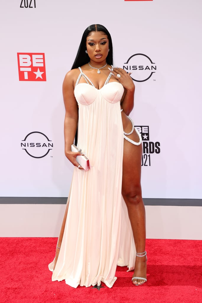 """There are thigh-high leg slits, and then there's Megan Thee Stallion at the 2021 BET Awards. The Good News rapper stepped out on Sunday night for the award show wearing an absolutely stunning gown by Jean Paul Gaultier. Megan's dress featured Gaultier's iconic cone bra with diamond hip chains connecting the sides of the dress in a beautiful pale pink colour. We simply could not take our eyes off her — and neither could her date! After making their red carpet debut at the iHeartRadio Music Awards in May, Megan and her boyfriend, Pardison """"Pardi"""" Fontaine, were back at the BET Awards looking smitten and cute as ever.  It's a big night for the rapper, as she's nominated for seven awards and is also taking the stage to perform. Check out photos of Megan Thee Stallion's super sexy Jean Paul Gaultier gown at the BET Awards ahead.      Related:                                                                                                           Please Place Your Attention on These Fabulous BET Awards Red Carpet Looks               all a"""