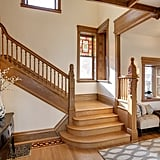 Vaulted ceilings and a wooden staircase lead to the second story of the home.