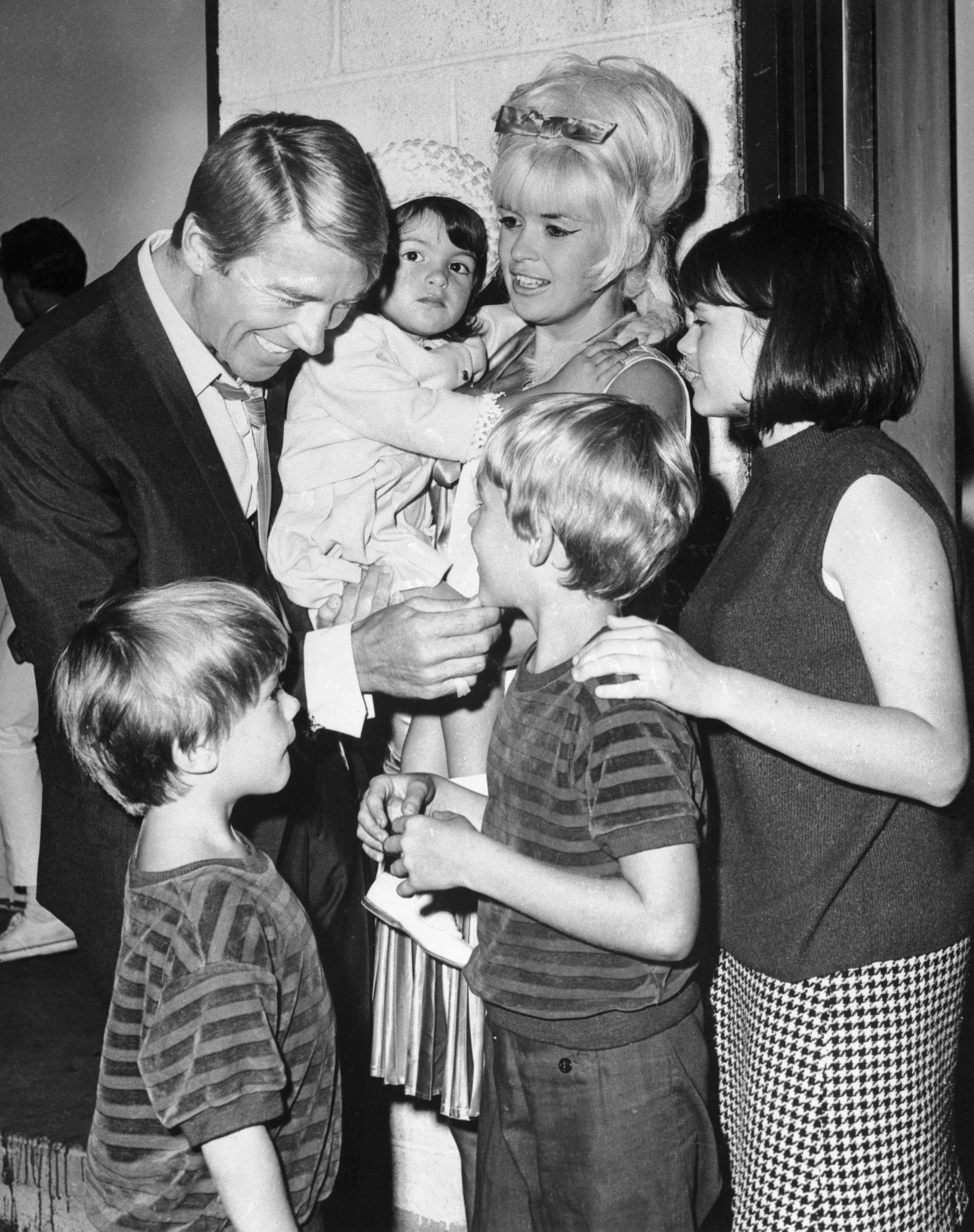 (Original Caption) Actor Mickey Hargitay is obviously enjoying his reunion with his former wife, actress Jayne Mansfield, and their children July 19th, backstage at the Westbury, L. I. Music Fair, where Miss Mansfield opened in Gentlemen Prefer Blondes. Hargitay flew in from Rome to be with his former wife, who was separated form her present husband, producer Matt Cimber, July 15th. The children are Zoltan, 5, Mikos, 7, and Mariska 2, and 14 year old Jayne Maria, Miss Mansfield's daughter by a previous marriage.