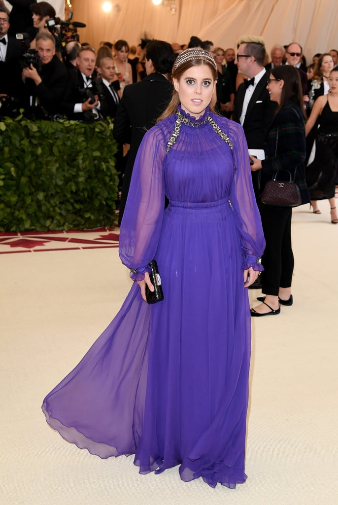 "It's the biggest night in fashion and it wouldn't be complete without a royal appearance! On Monday night, Princess Beatrice of York stepped out at the 2018 Met Gala bringing a splash of color to the swarm of gold gowns for the ""Heavenly Bodies: Fashion and the Catholic Imagination"" themed event. Her sheer, bright gown was styled with silver jewelry and a headpiece that made our jaws drop. The Princess was even hiding a pop of gold in her strappy heels.  It's less than two weeks before Prince Harry and Meghan Markle's royal wedding, and if her colorful look is any indication of what she'll wear on May 19, we've got high hopes. Photos of Princess Beatrice's royal purple gown ahead."