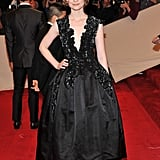 Showing off a little decolletage in a rosette-adorned black gown at the Met Gala in 2011.