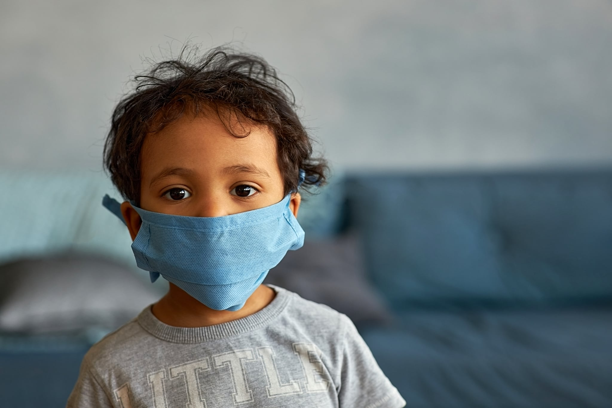 Portrait of a cute african american boy in mask at home - contagion of the Novel Coronavirus 2019- ncov - virus incubation isolation