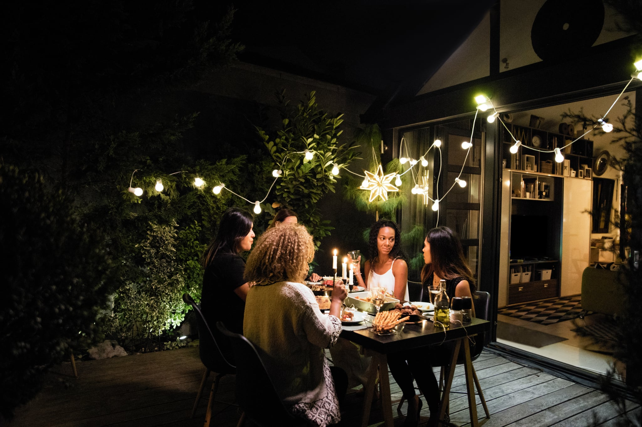 Latino women have dinner party at house yard