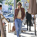 Wearing a pair of RE/DONE Levi's jeans with a cream top, a brown leather jacket, and pointed-toe shoes.