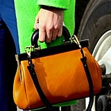 A chic satchel pops against a bright green coat.