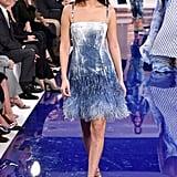 Walking in Ralph Lauren wearing a blue velvet dress that featured feathers.