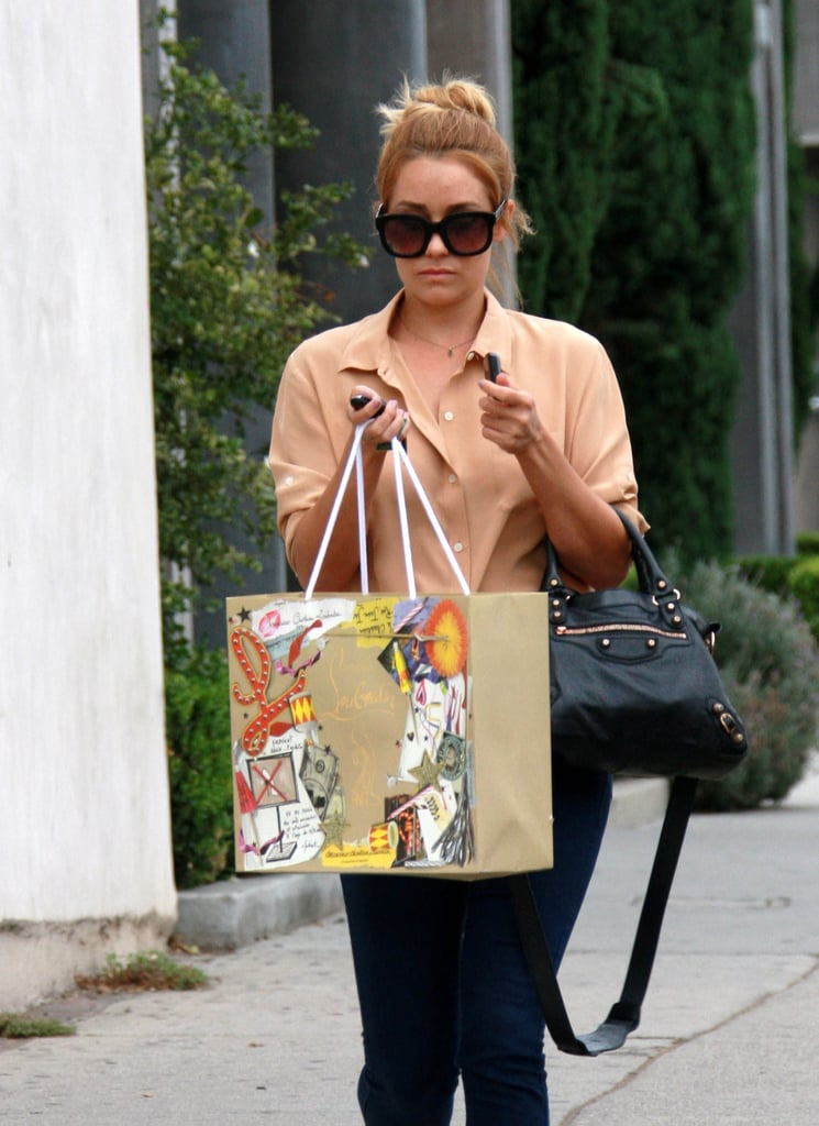 Lauren Conrad had her hands full yesterday carrying a Christian Louboutin bag while making a stop at West Hollywood's Madison boutique. She picked up a pair of nude Louboutin pumps embellished with a dainty bow and shared an Instagram snap of her latest luxury purchase. Bows are among LC's signature accessories, though she's also loving cutouts, one of the season's hottest trends.  LC's still modeling a slight golden glow from her recent trip to Mexico with boyfriend William Tell. The pair relaxed poolside at their Cabo resort and in between lounging in the sun and catching up on their Summer reading, they also shared some loving PDA.